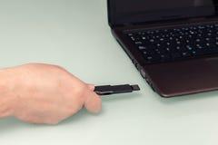 USB-Flash-Speicher an Hand mit Notebook Lizenzfreies Stockbild