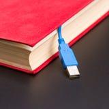 Usb-Kabel haftet heraus vom roten Buch Stockfoto
