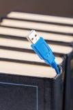Usb-kabel klibbar ut från böckerna Royaltyfri Fotografi