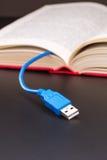 Usb-kabel klibbar ut från den röda boken Royaltyfria Bilder