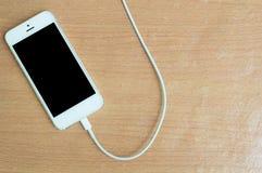 USB-Kabel mit Smartphone auf hölzerner Tabelle Stockfotos
