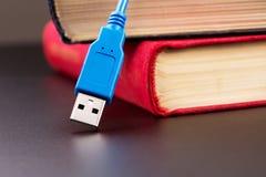 Usb-kabel och böcker Arkivbild