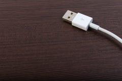 USB kabel på den wood tabellen Fotografering för Bildbyråer