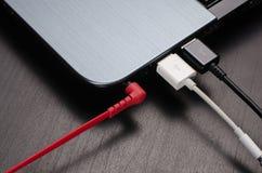 USB-kabels en hoofdtelefoonhefboom aan laptop wordt aangesloten die Stock Foto