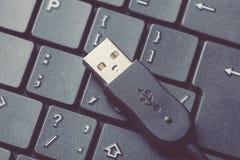 Usb-Kabelverbindungsstück auf einem schwarzen Laptoptastaturabschluß oben Getontes Bild Stockfoto