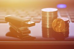 USB memory cards and a few coins lying on the body of black laptop in front of his keyboard. Virtual memory storage with USB outp. Ut and a small amount of money stock photos