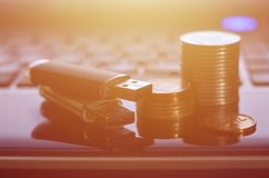 USB memory cards and a few coins lying on the body of black laptop in front of his keyboard. Virtual memory storage with USB outp. Ut and a small amount of money stock photo