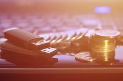 USB memory cards and a few coins lying on the body of black laptop in front of his keyboard. Virtual memory storage with USB outp. Ut and a small amount of money stock photography