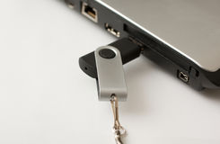 USB Memory stick plugged into laptop. Black and silver USB memory stick with keyring clip being plugged into a laptop, possibly sharing business documents, files Stock Photo