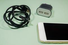 有usb缆绳和块适配器的一个电话 库存图片