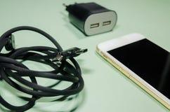 有usb缆绳和块适配器的一个电话 库存照片