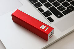 USB Powerbank and a computer. A red powerbank and a laptop computer Stock Photo