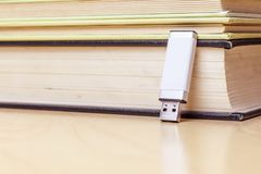 Usb stick with white hull leaning against a pile of books front view analog digital stock photography