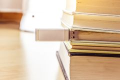Usb stick with white hull stuck between a pile of books top view analog digital stock photo
