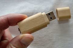 USB storage stick made of wood. Person holds USB stick of wood in hand Royalty Free Stock Photos