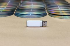 USB Universal Serial Bus stick in front on a stack of cd compact disc and dvd digital versatile optical disc stock photo
