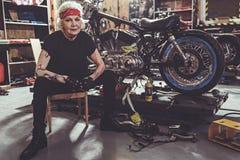 Uscente ritiri il posizionamento accanto al motociclo fotografia stock