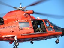USCG Helicopter Sector New Orleans in Flight. Close up shot of Coast Guardsmen looking out their helicopter as it flies through a clear blue sky Royalty Free Stock Images