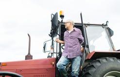 Uscire dell'agricoltore o dell'uomo anziano del trattore all'azienda agricola Fotografie Stock