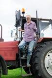 Uscire dell'agricoltore o dell'uomo anziano del trattore all'azienda agricola Fotografie Stock Libere da Diritti