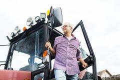 Uscire dell'agricoltore o dell'uomo anziano del trattore all'azienda agricola Immagini Stock