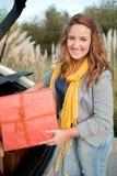 Uscire della donna della sua automobile con i presente Immagini Stock Libere da Diritti