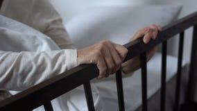 Uscire malato invecchiato della donna appena del letto che tiene sopra a recintare, reparto di ospedale stock footage