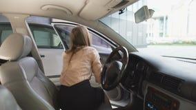Uscire piacevole della donna dell'automobile, mostrante biglietto da visita verde nella macchina fotografica, modello stock footage