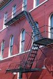Uscita d'emergenza su costruzione rossa Fotografia Stock Libera da Diritti