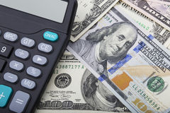 USD bank notes and a calculator Stock Images