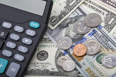USD bank notes with coins and a calculator Stock Image