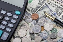 USD-Banknoten mit Münzen und einem Taschenrechner Lizenzfreies Stockfoto