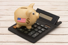 The USD dollar currency. A golden piggy bank and calculator on a wood background with US flag Royalty Free Stock Photos