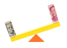 Usd heavier than rmb on teeterboard on white Royalty Free Stock Image