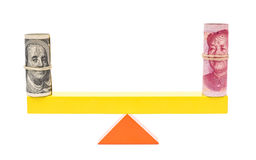 Usd and rmb balance on teeterboard on white Stock Images