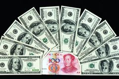 USD and RMB bank notes. Pile of USD and RMB bank notes on a black background Stock Images