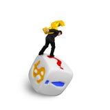 USD-Symbol Gold des Geschäftsmannes tragendes, das auf Würfeln balanciert Stockfotos