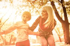 We always use the best autumn day. Young mother with her daughter enjoying in park together. Close up royalty free stock image