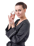 The use of cosmetics for skin care. Real young woman in a black bathrobe over a white background Stock Photos