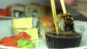 Sushi and sauce to the table. The use of fish dishes of sushi with sauce laid out on the table stock footage