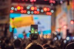 Use gravação móvel avançada, concertos do divertimento e a iluminação bonita, imagem cândido da multidão no concerto de rocha, fe imagem de stock royalty free