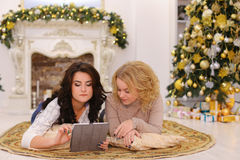 Use of modern gift gadget by two sisters lying on floor in brigh. Charming cousins look at tablet and enjoy New Year`s gift from their parents. Girls drive their Royalty Free Stock Image
