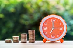 Use money investment to save time and resources concept. Stacking coins in 1 to 4 step with white orange clock on table over green nature background royalty free stock images