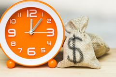 Use money investment to save time and resources concept. US dollar in moneybag with white orange clock on wooden table background. Demonstrate the growth of stock images