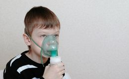 Use nebulizer and inhaler for the treatment. Boy inhaling through inhaler mask. Front view stock image