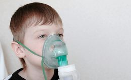 Use nebulizer and inhaler for the treatment. Boy inhaling through inhaler mask. Front view royalty free stock photo