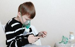Use nebulizer and inhaler for the treatment. Boy inhaling through inhaler mask and playing the game in his mobile phone royalty free stock photography