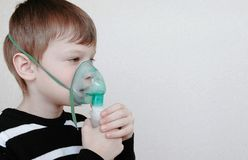 Use nebulizer and inhaler for the treatment. Boy inhaling through inhaler mask. Side view. stock photo
