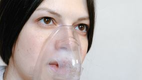 Use nebulizer and inhaler for the treatment. Closeup woman`s face inhaling through inhaler mask. Front view. Use nebulizer and inhaler for the treatment stock video footage