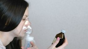 Use nebulizer and inhaler for the treatment. Closeup woman`s face inhaling through inhaler mask. Side view. Use nebulizer and inhaler for the treatment. Closeup stock footage